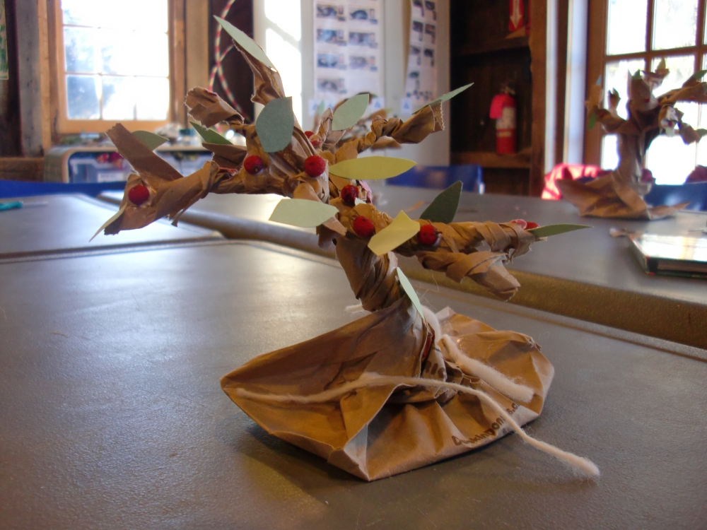 My son's finished tree, with paper leaves and flowers, dried winterberries for the apples, and spun wool for the roots.