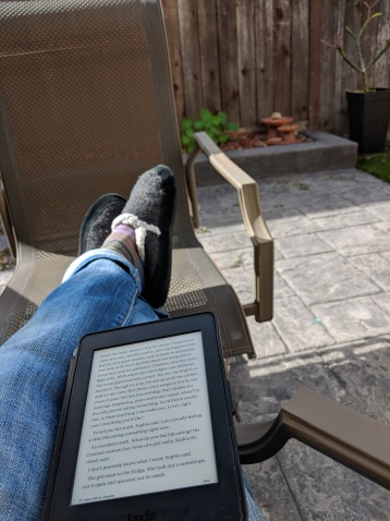 Feet clad in gray slippers crossed and propped on a brown chair on a sunny patio. The legs are in blue jeans and a Kindle Paperwhite is resting on them..