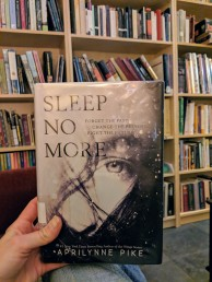 A hand holding a book in front of a bookshelf. The cover of the book has a black-and-white image of a woman's face overlaid with the title Sleep No More and the words Forget the Past, Change the Present, Fight the Future. Aprilynne Pike is printed across the bottom of the book cover.